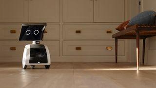 Roboten Amazon Astro foran et skap og ved siden av en benk på noe som ser ut som et soverom