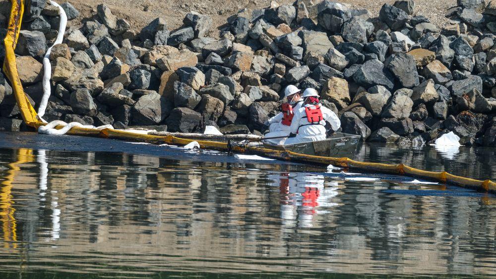 Mannskaper jobber med å begrense skadene fra oljeutslippet i Huntington Beach i California.