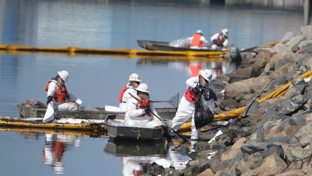Oljen har lagt seg tjukt i vannet, og mannskaper jobber på spreng for å begrense miljøskadene.