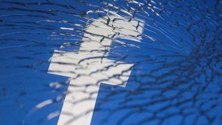 Facebook-logoen sett gjennom knust glass.
