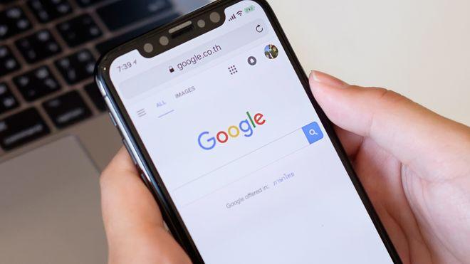 Nærbilde av noen som holder en Iphone med Google-søkemotoren på skjermen.