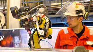 Robotoperatør Kristian Rundhovde Økland overvåker tester med automatisk robotsveising av aluminiumsprofiler.