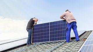 To menn monterer solcellepaneler på tak.