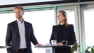 Astrup og Hofstad Helleand. Mann og dame i dress står foran et vindu.