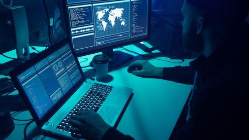 En mann sitter i et mørkt rom og koder på en maskin