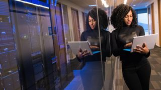 Kvinne med PC lener seg på glassvegg og bak den er en gigantisk server