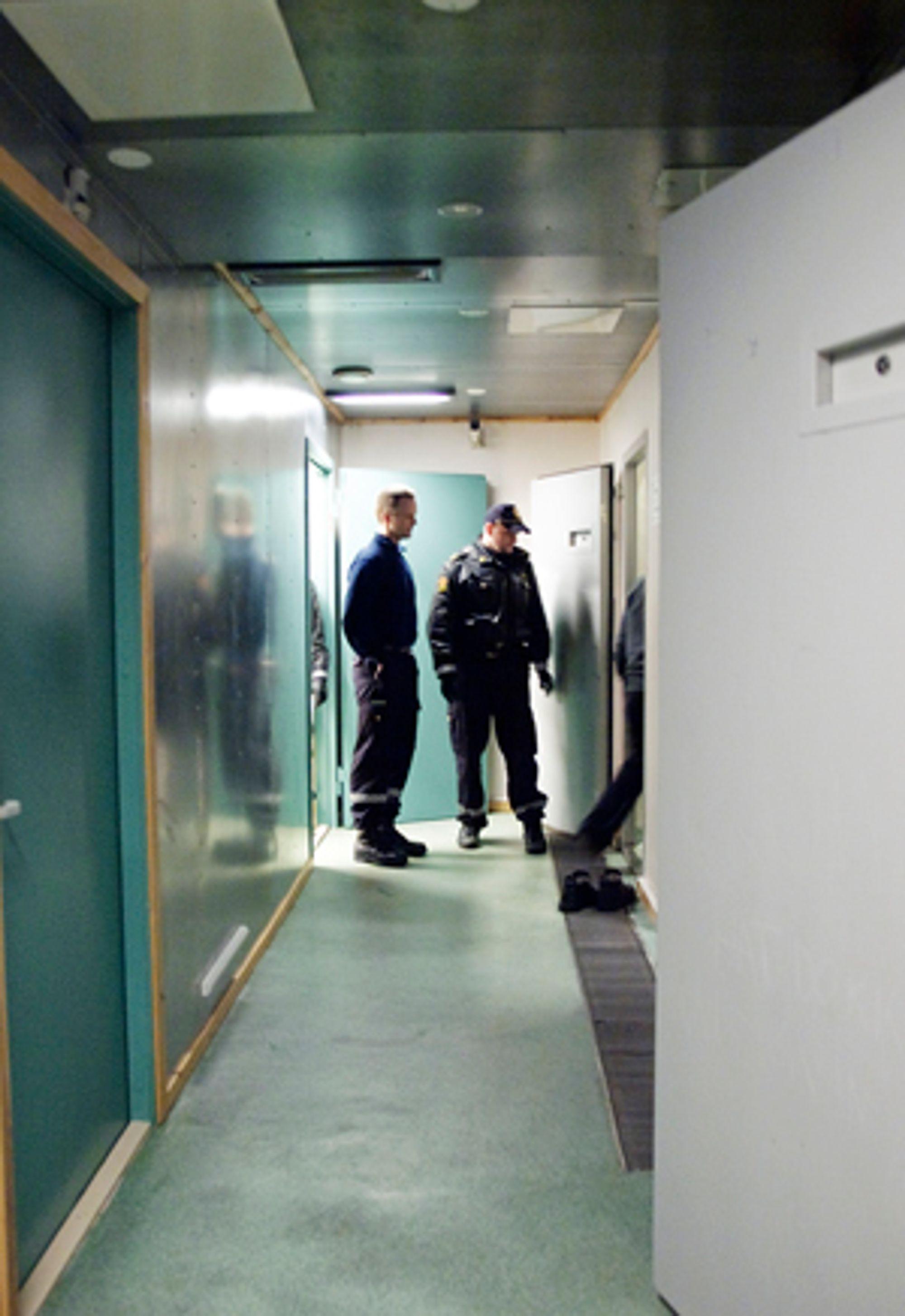 Arrestanten føres inn i cellen. © 2008 Simon Aldra.