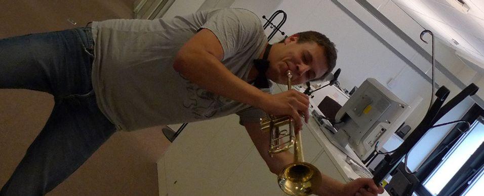 Fagredaktør Einar Eriksen her avbildet i heftig omgang med en trompet og et hattstativ.