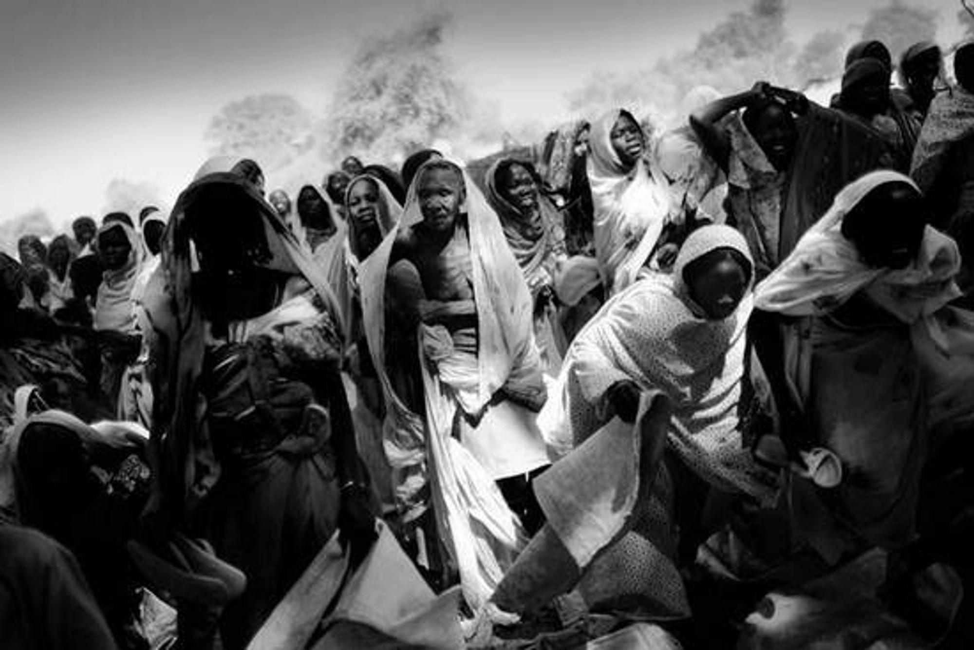 Habile, østre Tsjad, november 2006. Interne flyktninger venter på matrasjoner nærlandsbyen Habile. Habile pleide å være en liten landsby med noen få hundre innbyggere, men nå har titusenvis av mennesker søkt tilflukt der på grunn av angrep fra Janjaweed. © Jan Grarup / NOOR