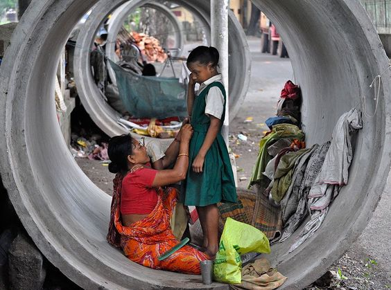A homeless mother preparing to send her daughter to school in the morning, while her still sleepy son clings to her in India. Foto: Gautam Basu ( BULLS/EPOTY.ORG )