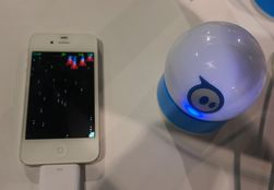 En Sphero-ball i ladekrybbe ved siden av en iPhone.