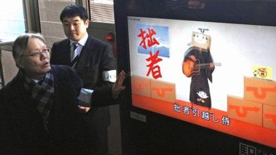 Direktør Takashi Yamamoto demonstrerer hvordan automaten har et kamera som kjenner igjen ansikter som går foran maskinen.